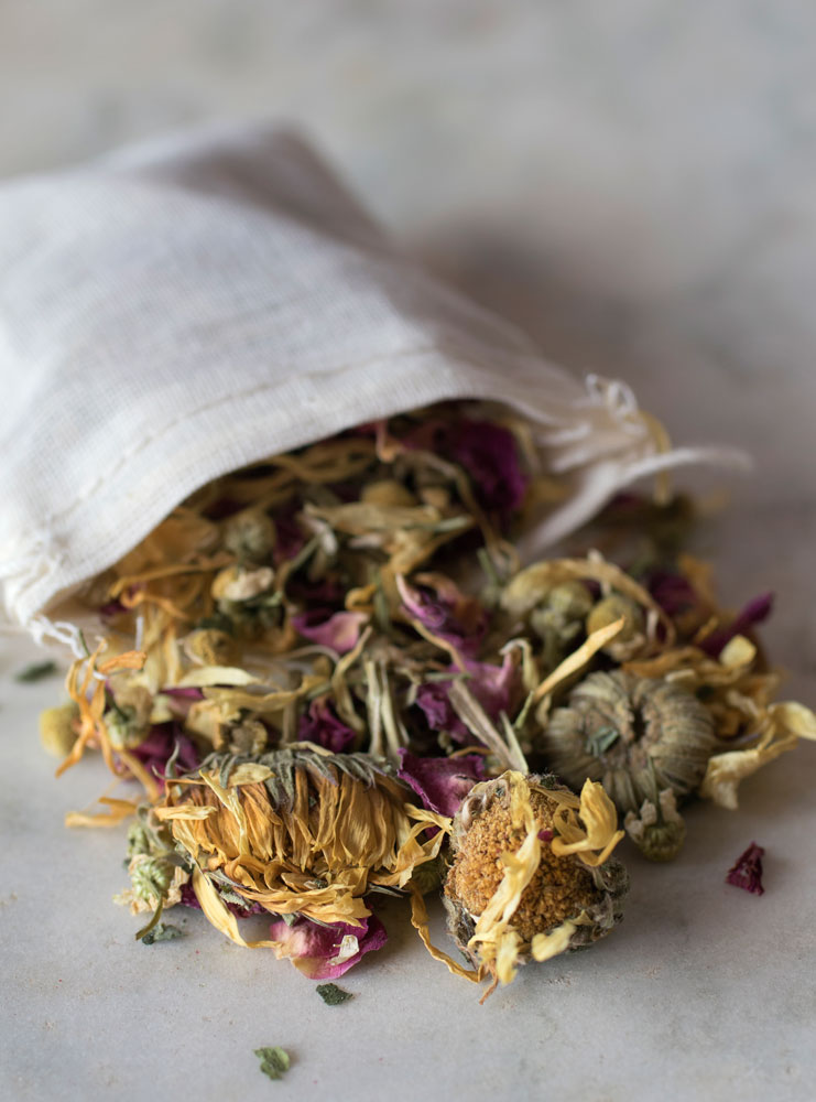 Close up of bath herbs spilling out of muslin bag on white surface