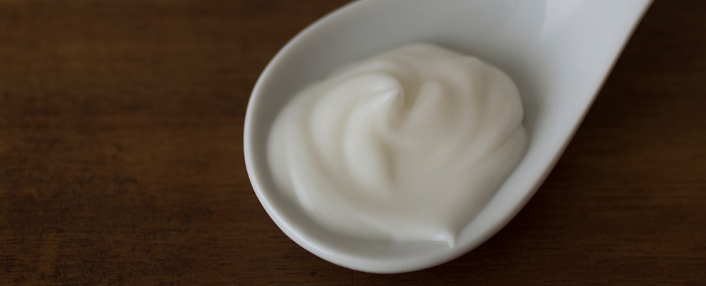 Homemade lotion on a glass spoon