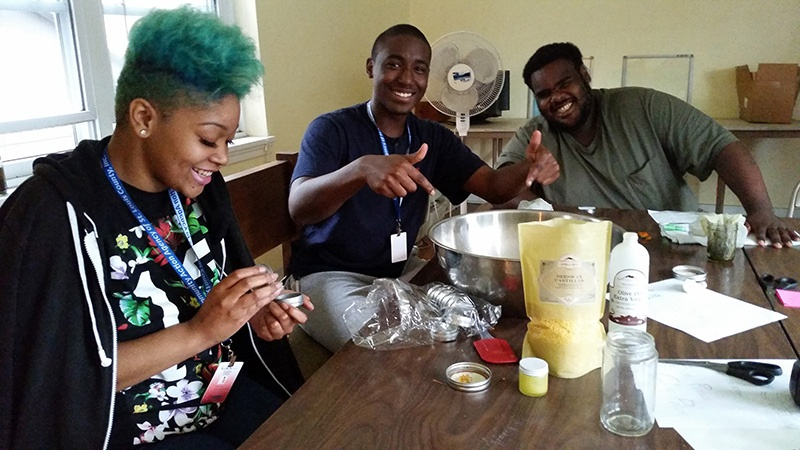 Teens smiling and making herbal preparations at the St. Louis Seeds of Hope Farm