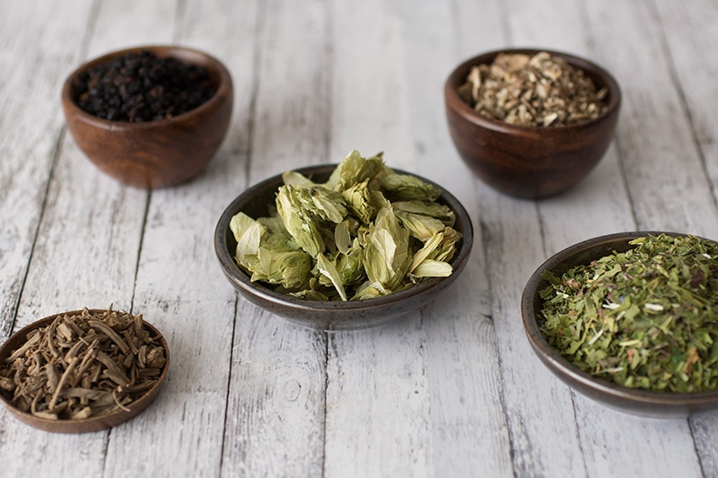 Wooden and ceramic bowls of dried herbs for making tinctures on a light wooden table.