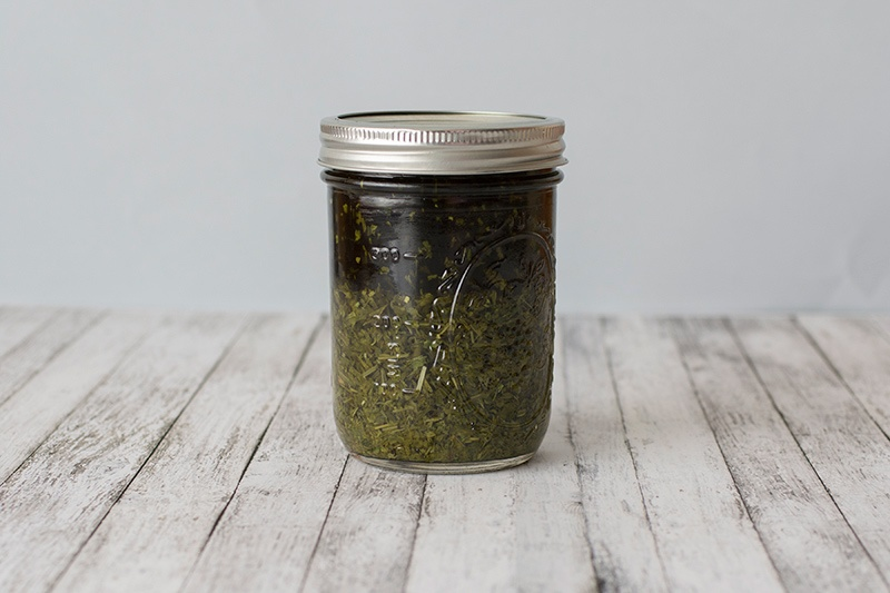 Glass jar full of herbs tincturing on a wooden table with white background.