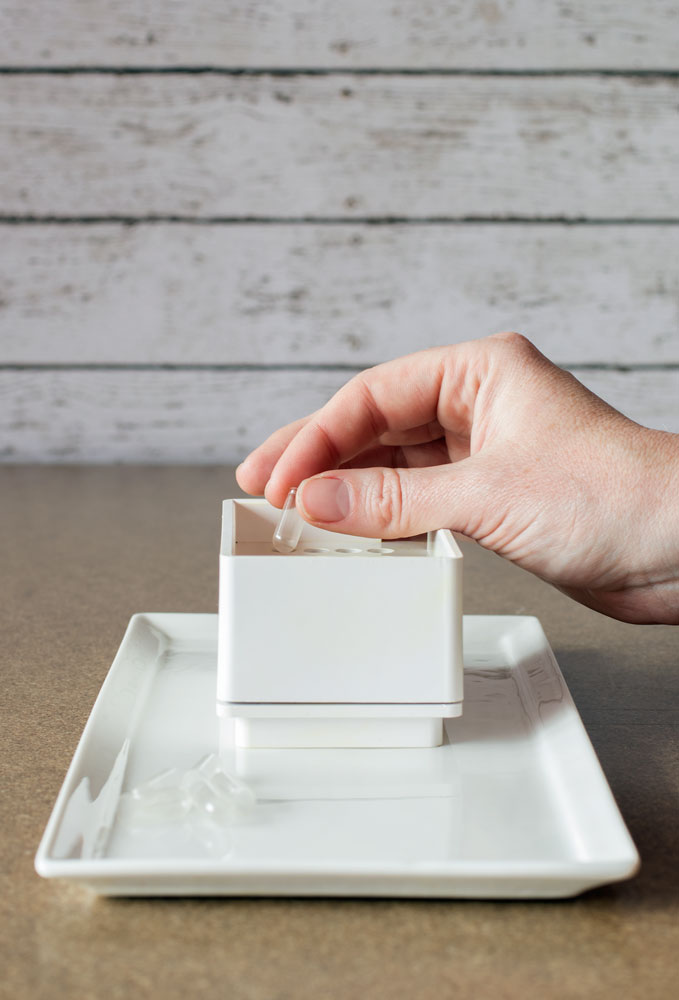Hand placing empty capsule into white plastic capsule machine on porcelain plate base