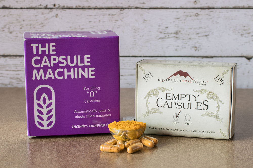 The Capsule machine and empty capsules in their boxes with a bowl full of turmeric powder and capsules of turmeric