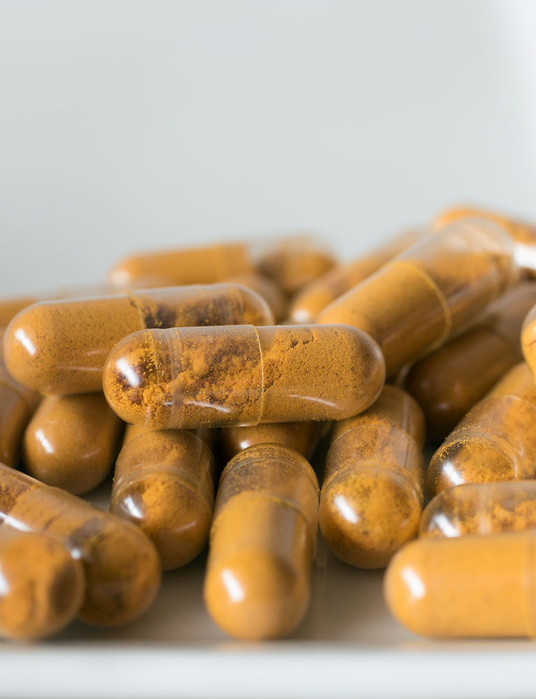 Capsules of turmeric made with the capsule machine on white background