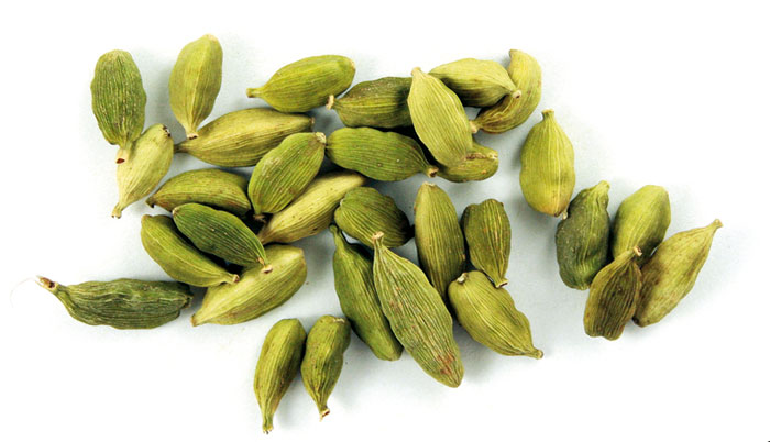 organic cardamom pods on a white background