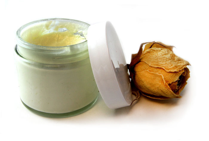 Glass jar of face cream with white lid and dried rose