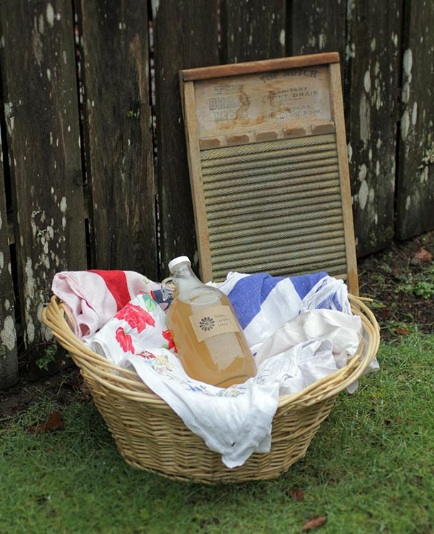 Homemade laundry formula in laundry basket full of clean clothes next to fence and old washing board