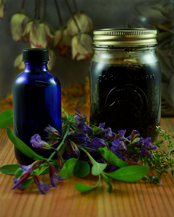 Jar of herbal liniment with herbs on table