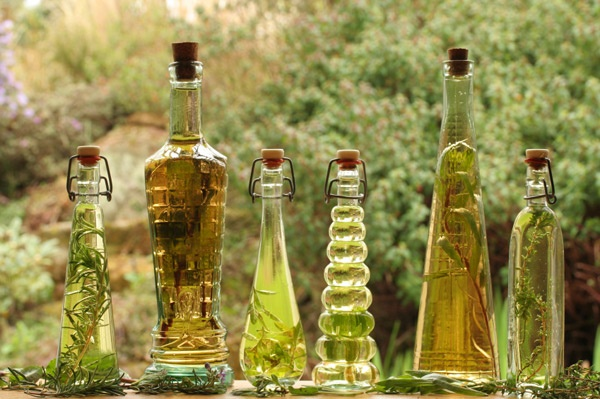 Bottles of oil with herbs infusing on a window sill