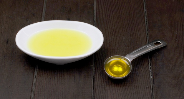 melted oils for whipped body butter recipe in bowl on table with measuring spoon