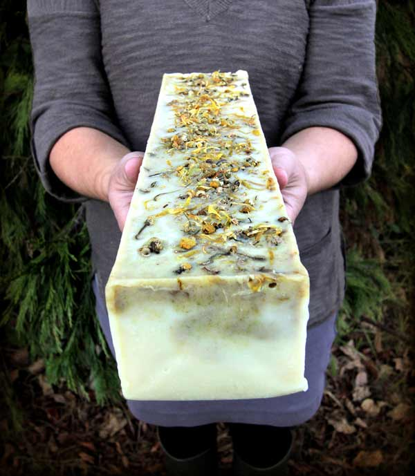 Person in gray dress holding block of finished soap with calendula and chamomile petals on top