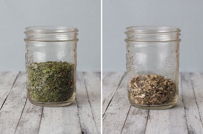 Dried herbs and roots in mason jars on light wooden table with blank background.