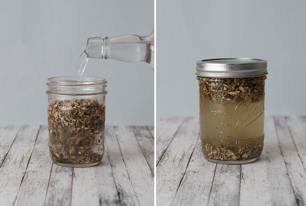 Alcohol being poured over herbs for tinctures in glass mason jars on wooden tabletops with white background.