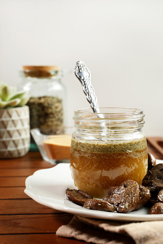Italian herb and garlic ghee in glass jar with spoon.