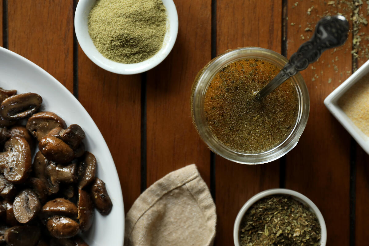 Italian herb and garlic infused ghee with bowls of organic seasonings and sauteed mushrooms.