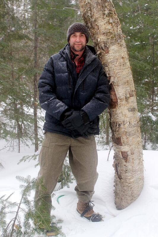 Handsome young man in snow gear leaning against tree in a snowy forest while pursuing organic, wildharvested chaga mushrooms.
