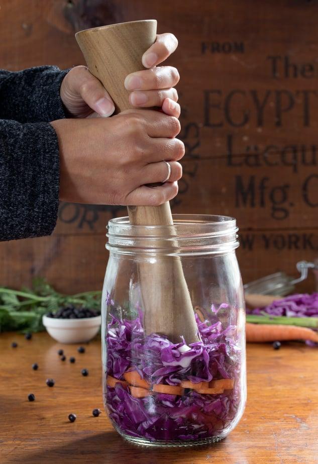 Hands using wooden pestle to massage cabbage to make sauerkraut in a glass jar