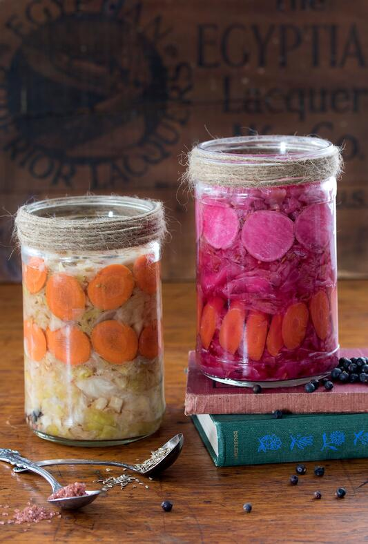 Jars of colorful homemade sauerkraut with ingredients around them