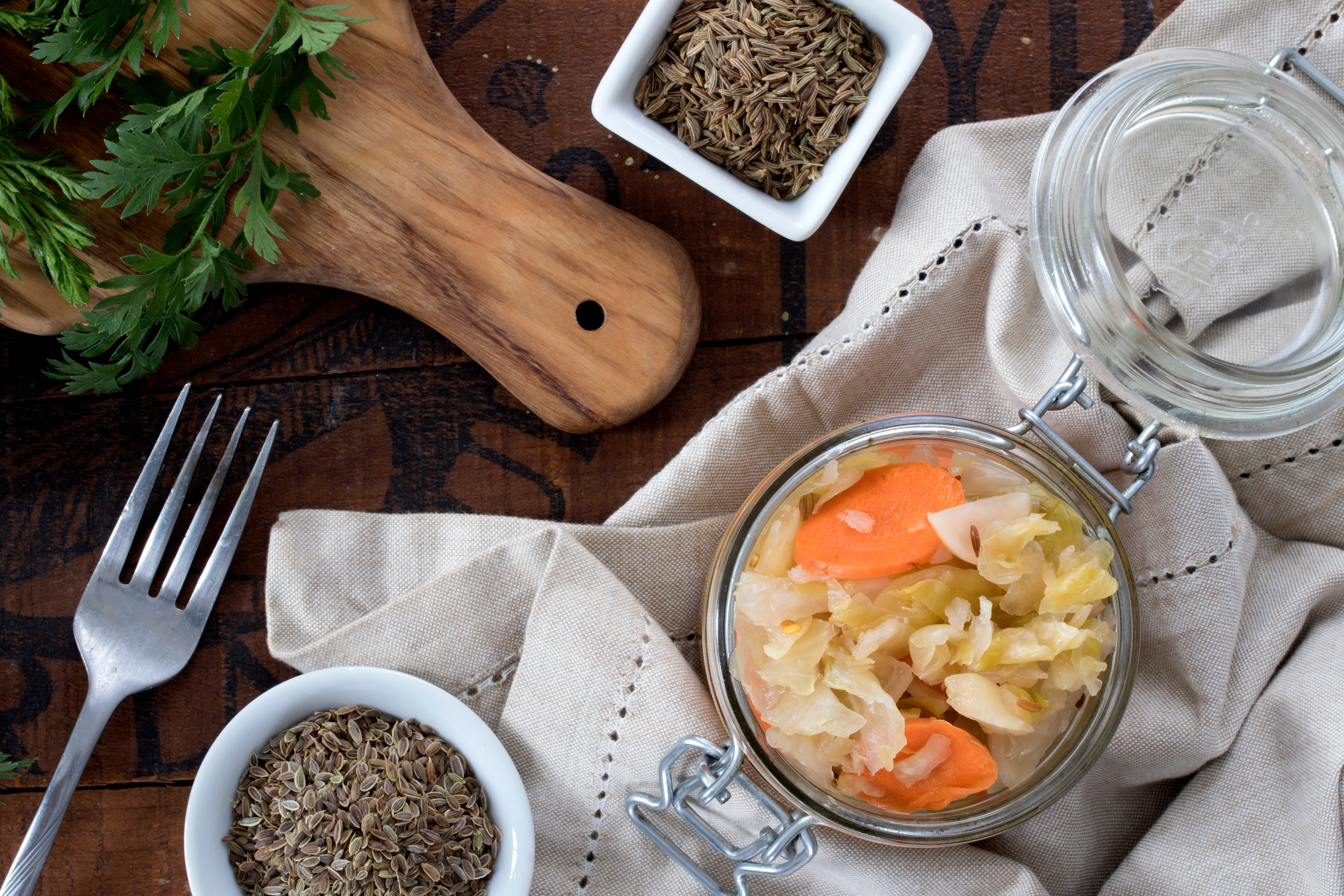 Glass jar of seeded sauerkraut with caraway seeds and mustard seeds with napkin and fork