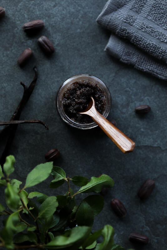 A DIY body scrub with vanilla and jojoba meal, honey, and coarse sea salt in a small glass salve jar. A wooden spoon is sitting in the salt scrub. Fresh jojoba beans are scattered around.