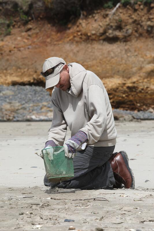 Jonathan kneeling on sand with bucket to pick up trash on the beach while helping with volunteer work