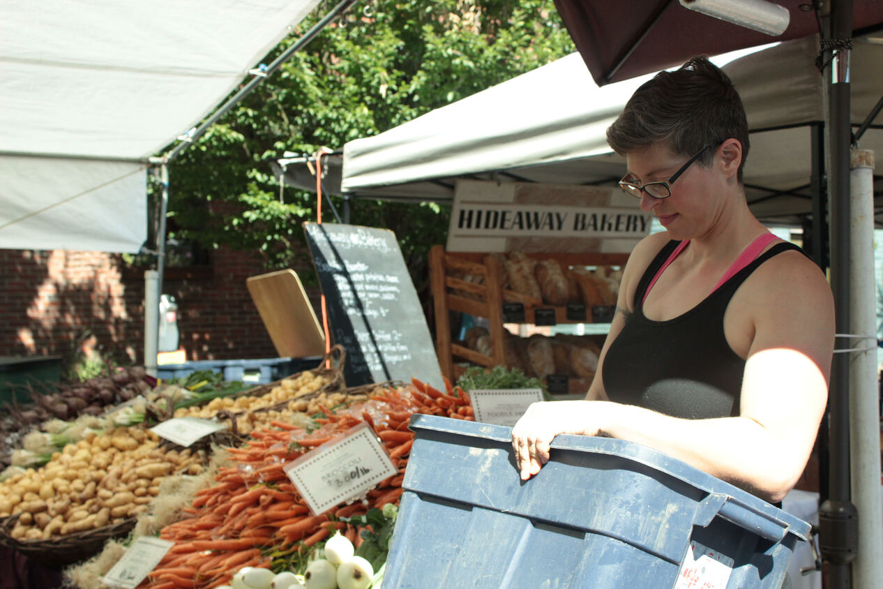 Working a local farmer's market featuring fresh produce like potatoes, carrots, and onions.
