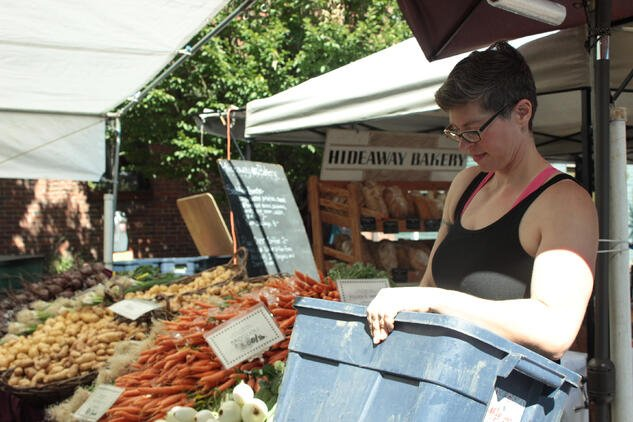 Julia, Mountain Rose Herbs Employee, working at a local farm stand at farmers market with fresh vegetables