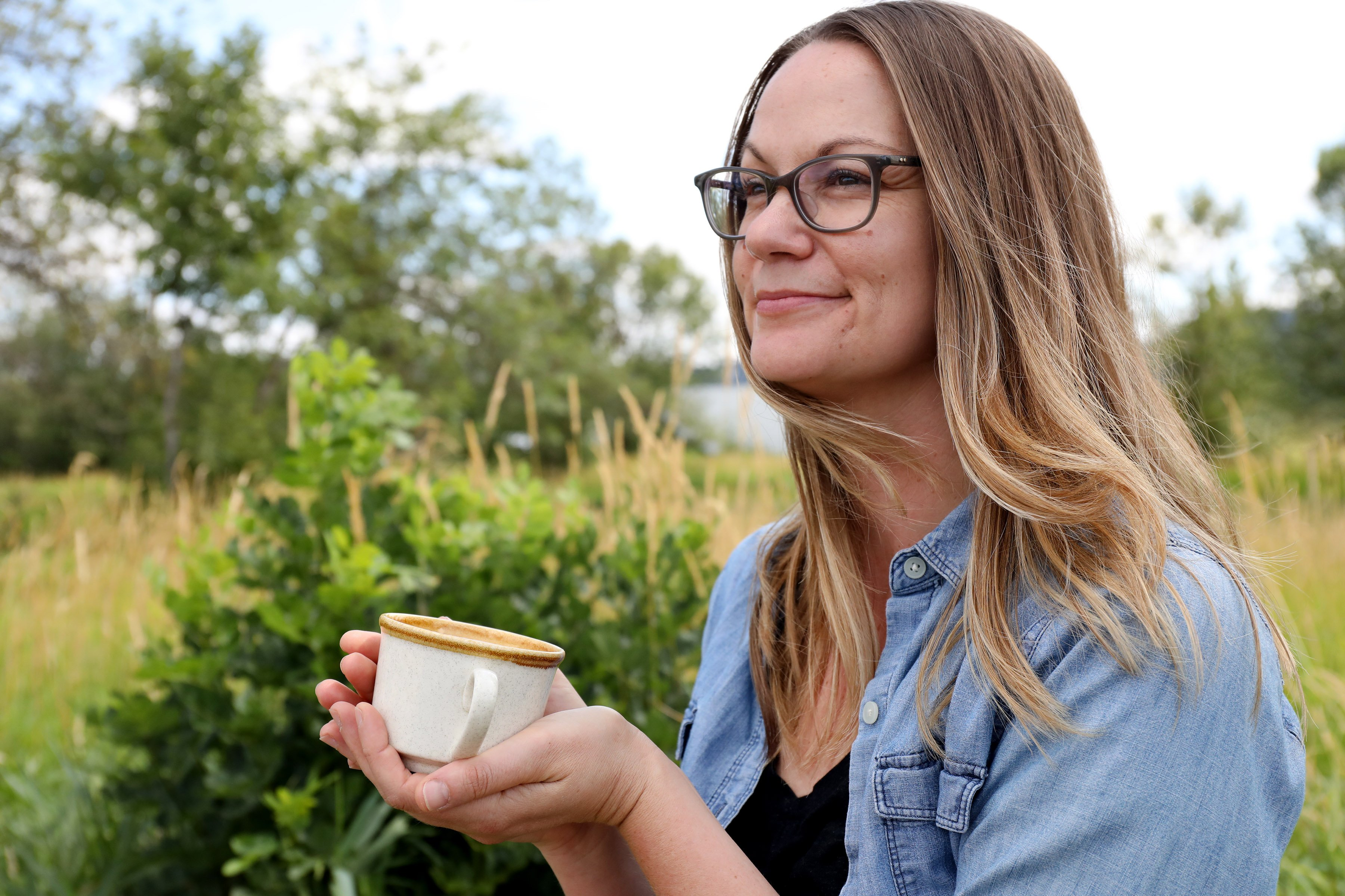 Production manager of Mountain Rose Herbs, Julie DeBord, sips a cup of organic herbal tea near the protected wetlands at our facilities in Eugene, Oregon.