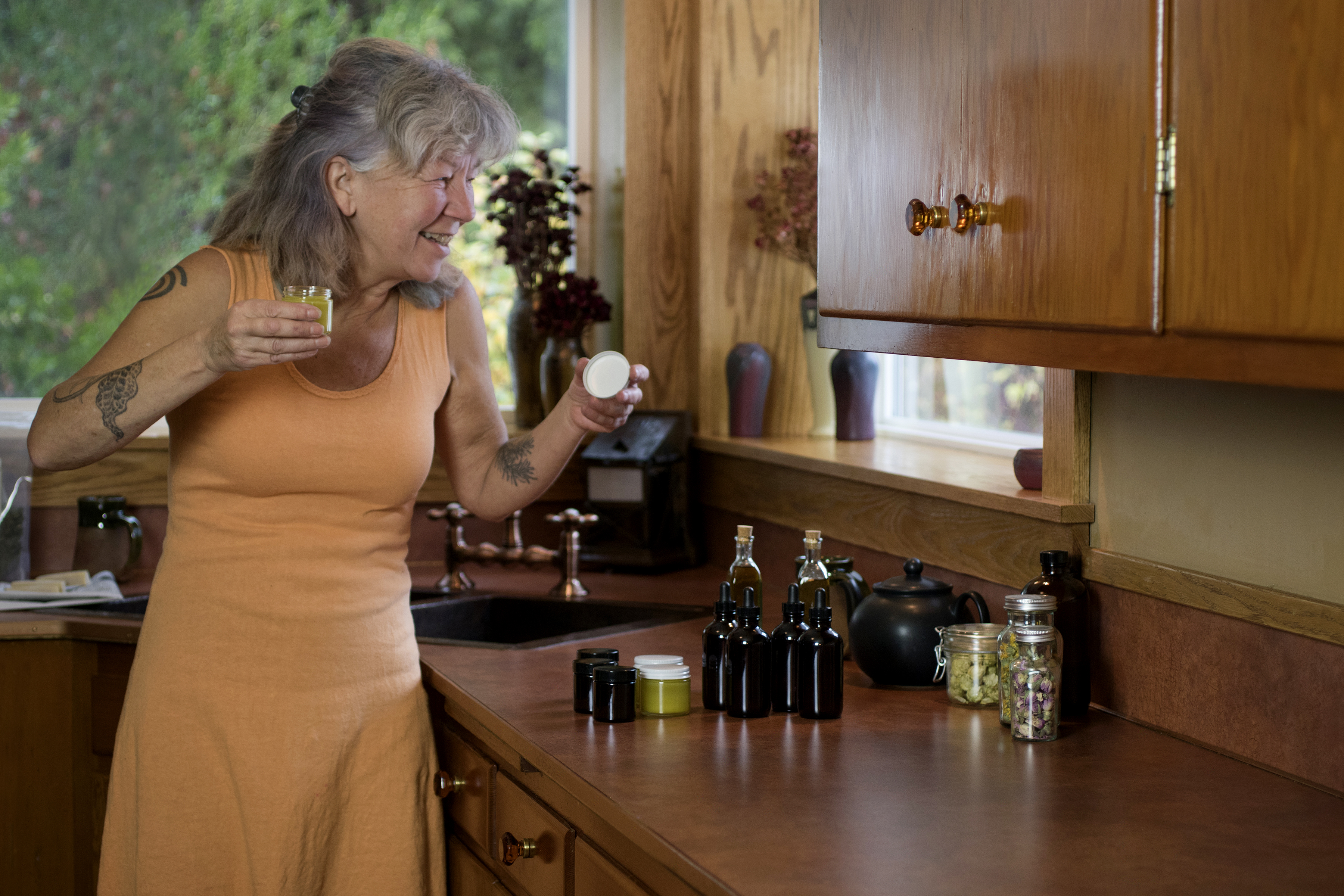Owner Julie Bailey and her small collection of homemade herbal salves and oils for testing in her home kitchen.
