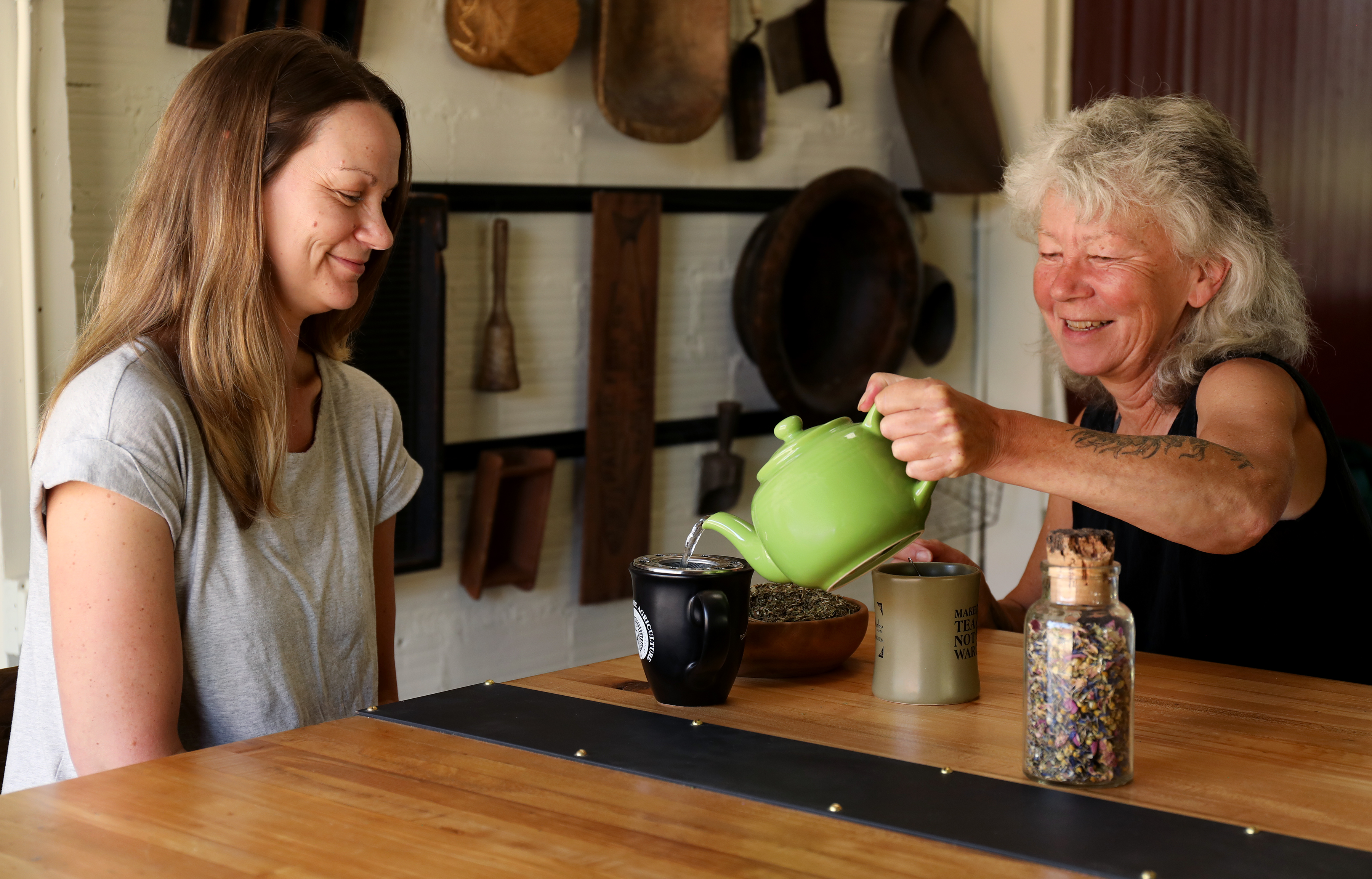 Co-owner Julie Bailey pours production manager Julie DeBord a cup of peace tea blend from Mountain Rose Herbs.