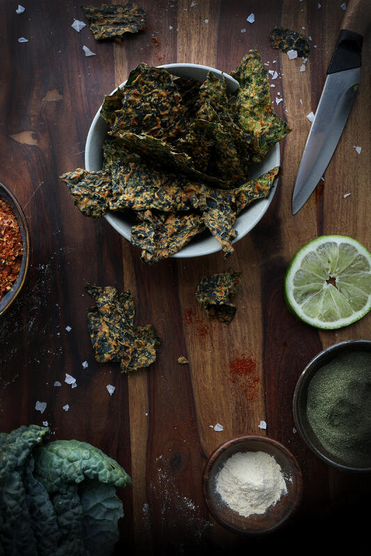 A ceramic bowl filled to the brim with spicy kale chips. Surrounding the bowl are various ingredients, fresh lime, chili flakes, fresh kale, and powders, all on a wooden cutting board.