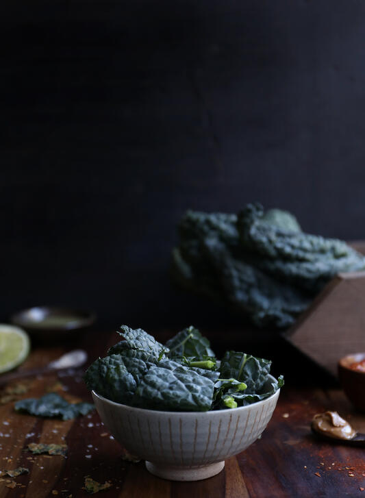 A white ceramic bowl filled to the brim with fresh organic Italian kale on a wooden cutting board.