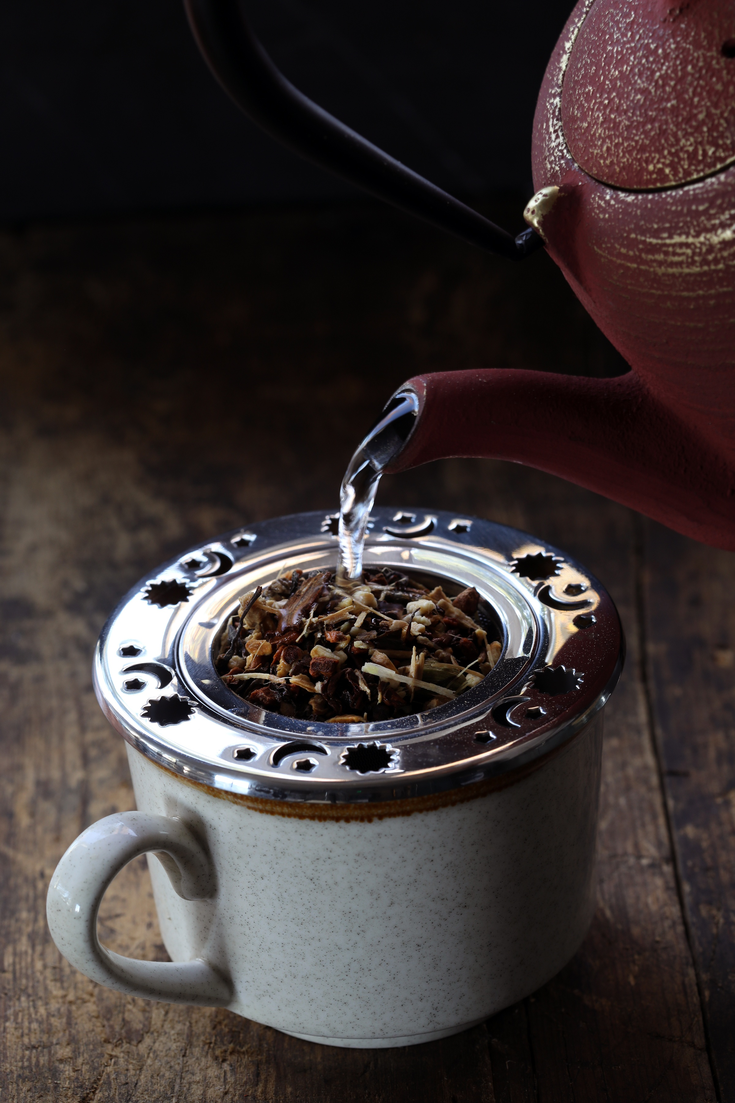 Tea kettle pouring hot water into mug holding celestial tea strainer filled with loose leaf tea