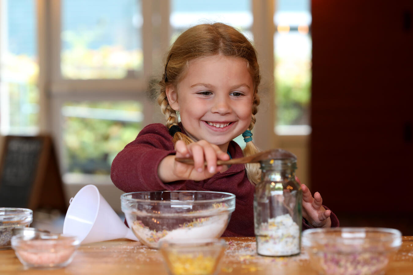 Child scooping salts in a jar