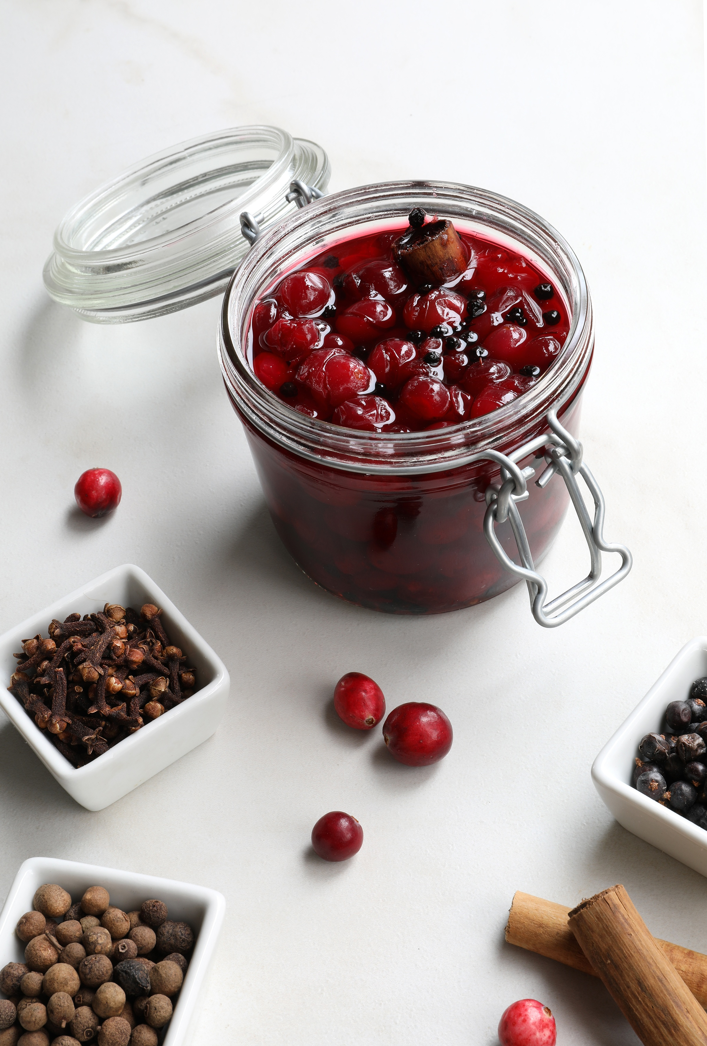 Canning Jar with pickled crannberries inside on counter with dried herbs and spices