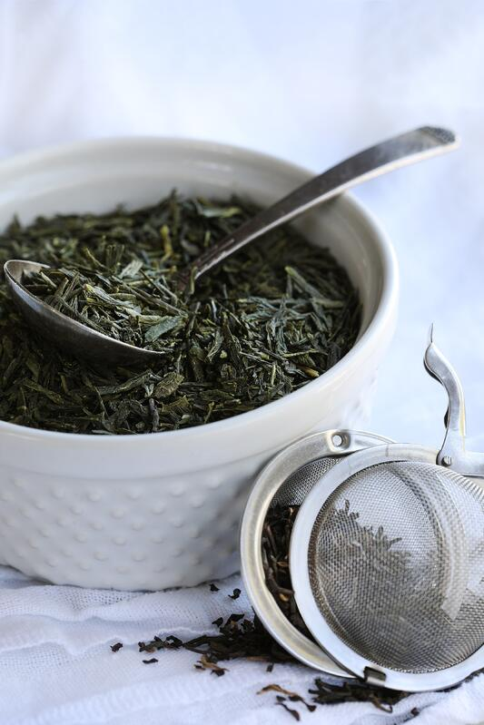 Fresh looking green tea in white [porcelain bowl with spoon and tea infuser filled with tea