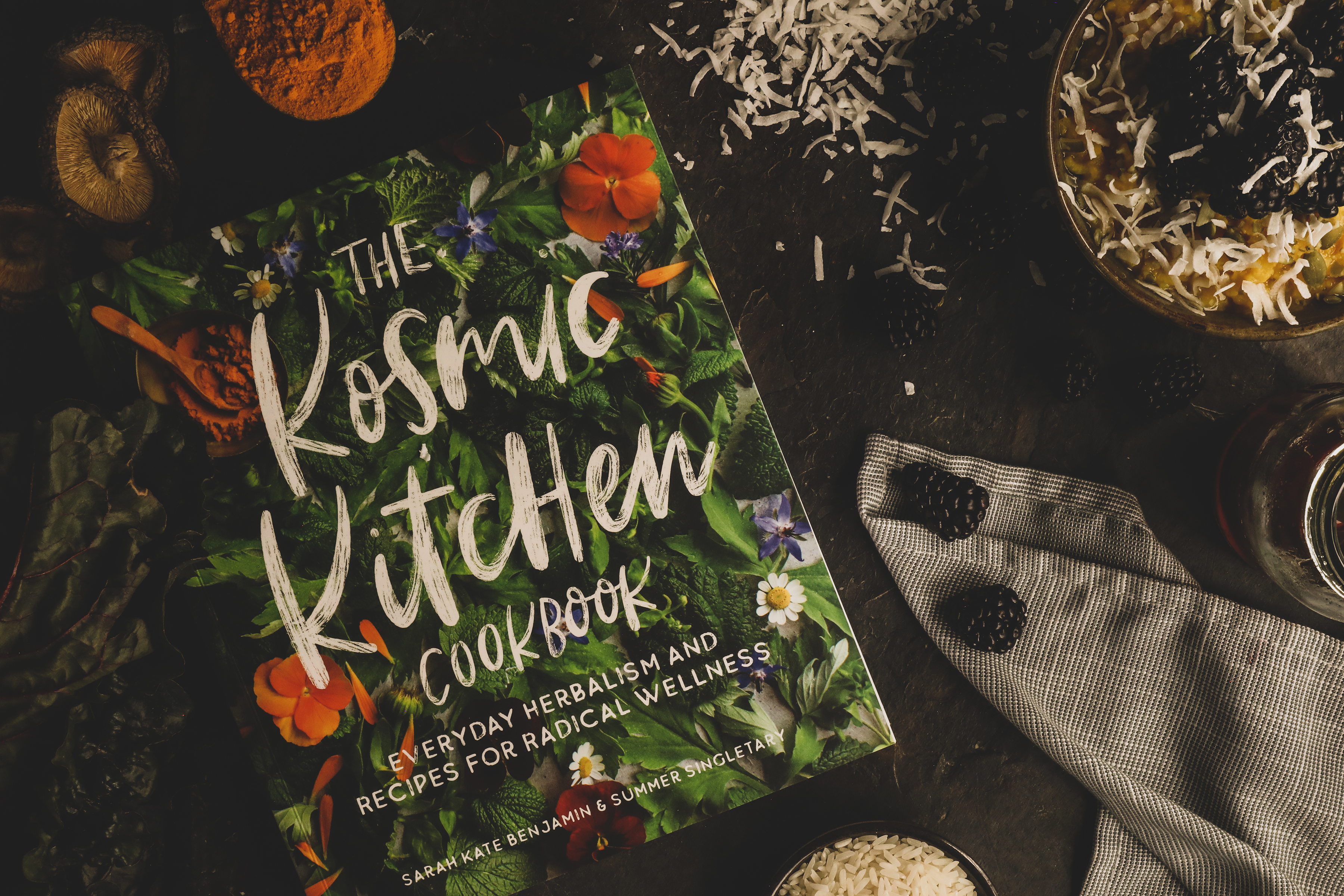 Kosmic Kitchen book surrounded by colorful ingredients.