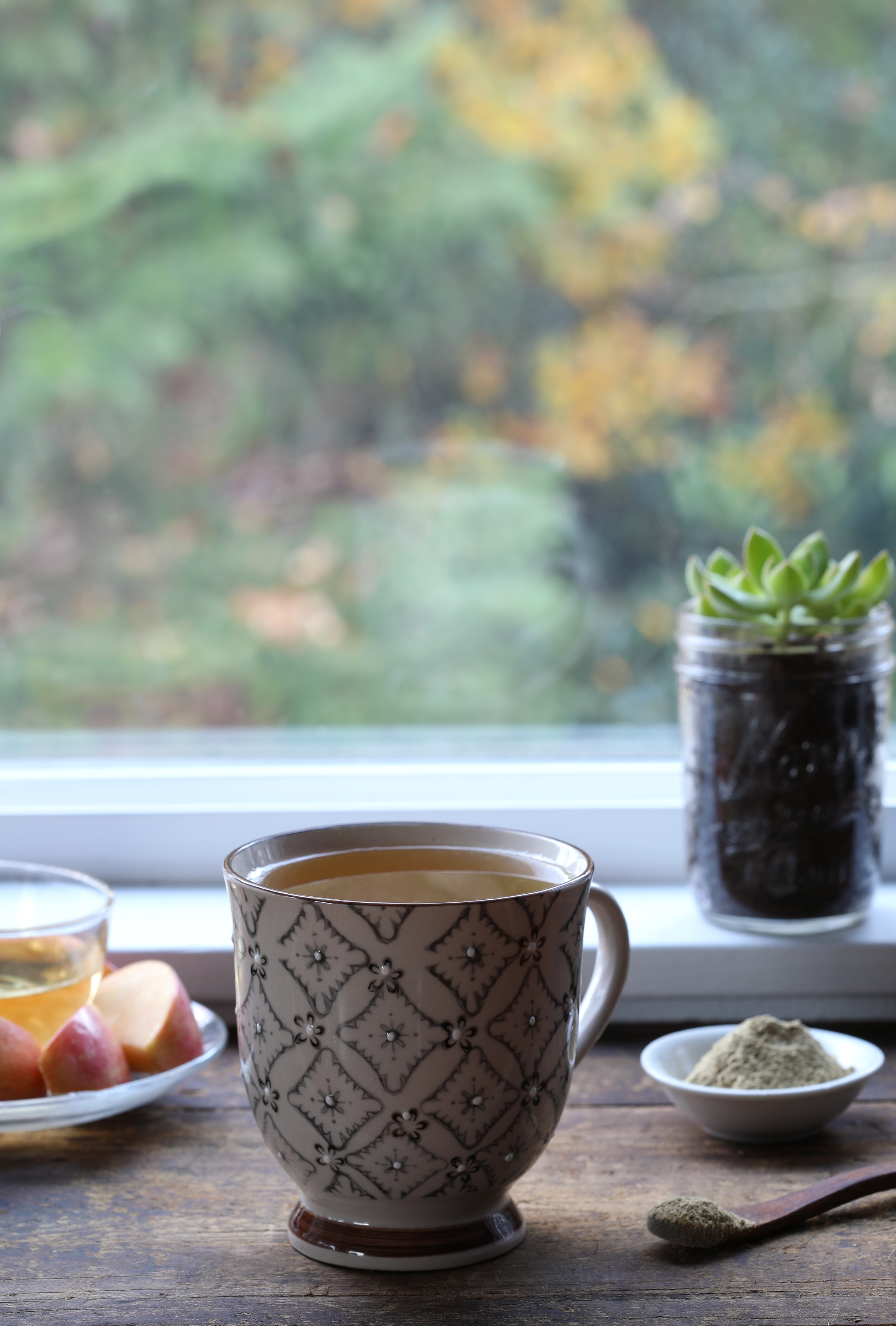 Ceramic mug filled with kava kava tea made from a french press sitting on window sill