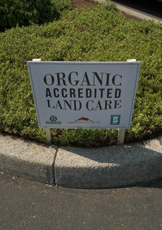 Sign on grass saying Organic Accredited Land Care at Mountain Rose Herbs headquarters and facilities