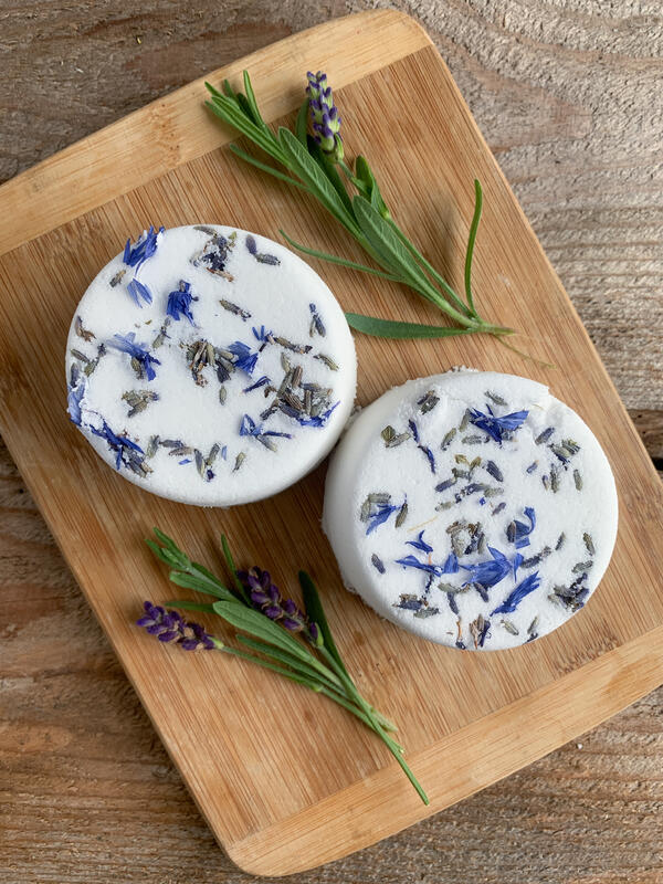 Two handmade bath bombs mixed with dried lavender flowers on a wooden cutting board surrounded by fresh sprigs of lavender