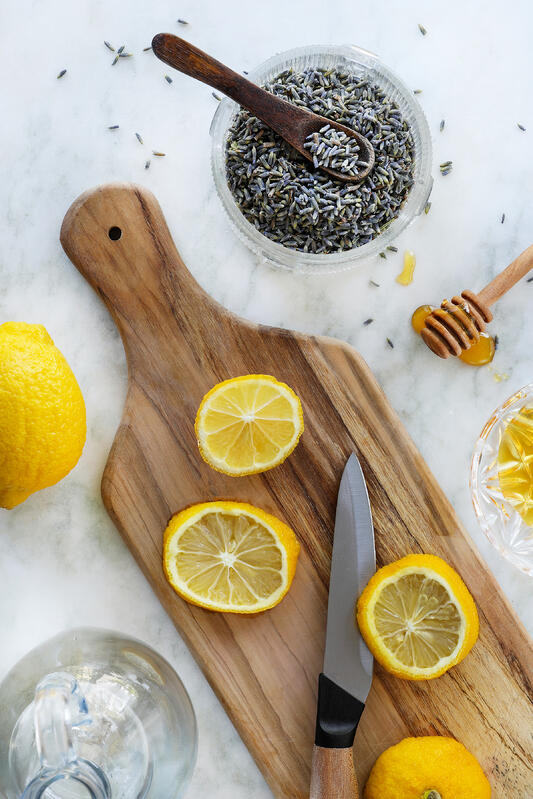 Ingredients for a lemon lavender soda are arranged with a wooden cutting board on a white marble countertop. Honey, fresh lemons, lavender flowers alongside a knife and honey scooper.