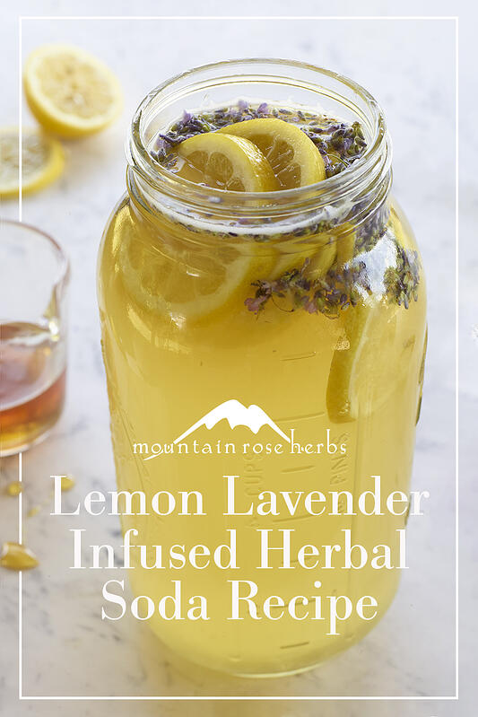 A large clear mason jar filled to the brim with finished lemon lavender herbal soda and garnished with fresh slices of lemon and lavender flowers on a white marble countertop.
