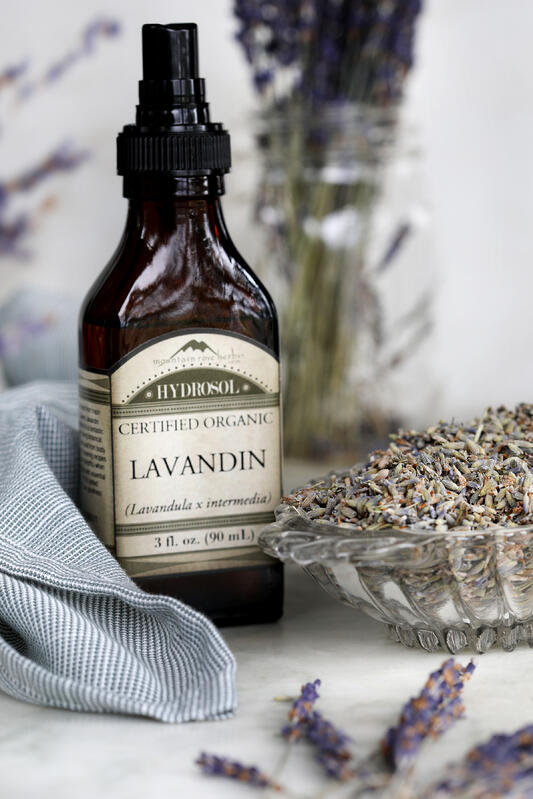 Lavandin hydrosol is a byproduct of essential oil making and serves as a floral base for skin care products or as an anytime spray for aromatherapy. Arranged with dried english lavender flowers.