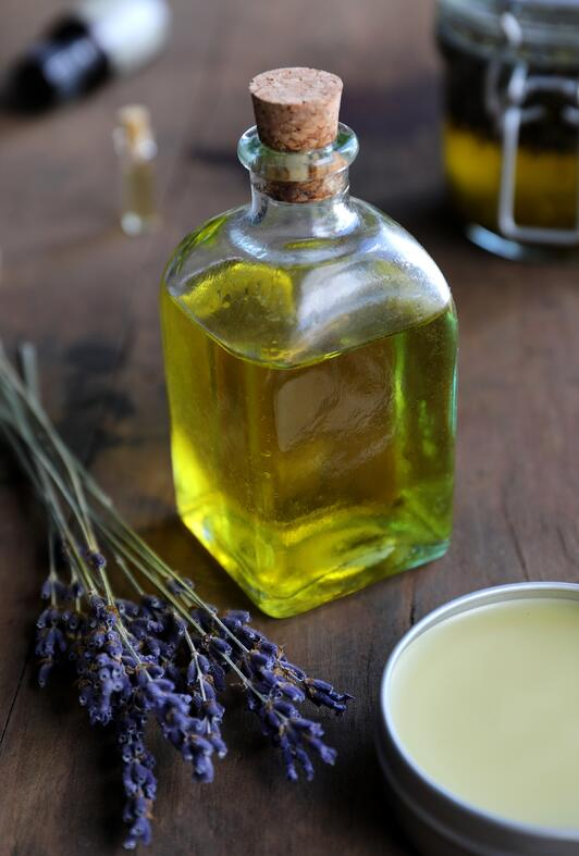 Vintage cork top glass bottle with oil in it with lavender and salve displayed in background.