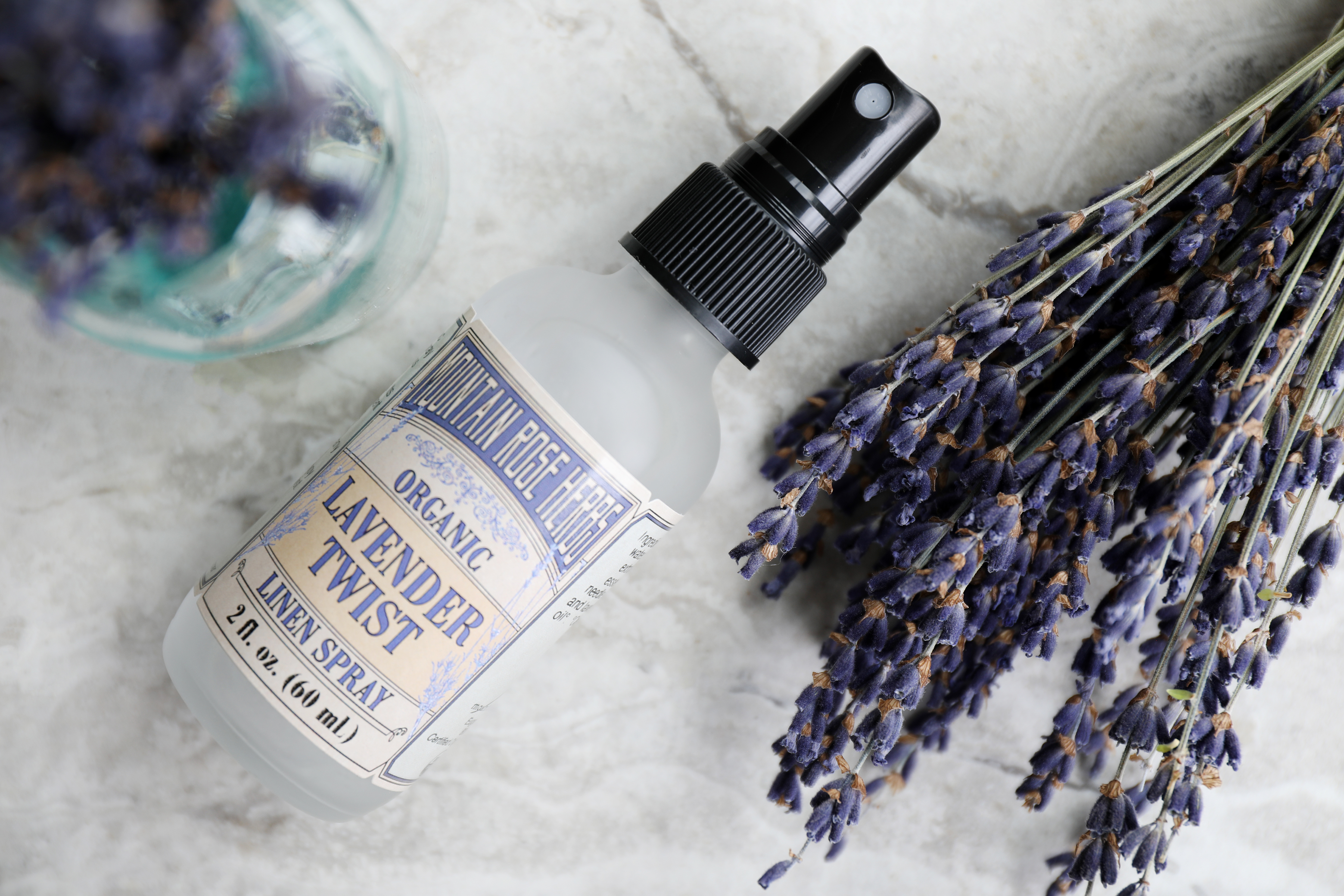 Bottle of Lavender Twist Aroma Spray with fresh sprigs of Lavender flowers.