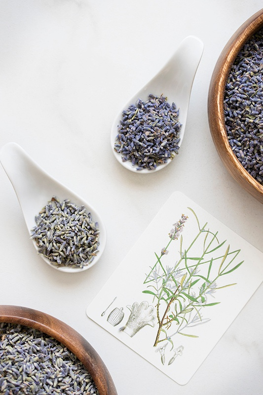 Spoonfulls of lavandin and lavender flowers on counter with herb card and bowl