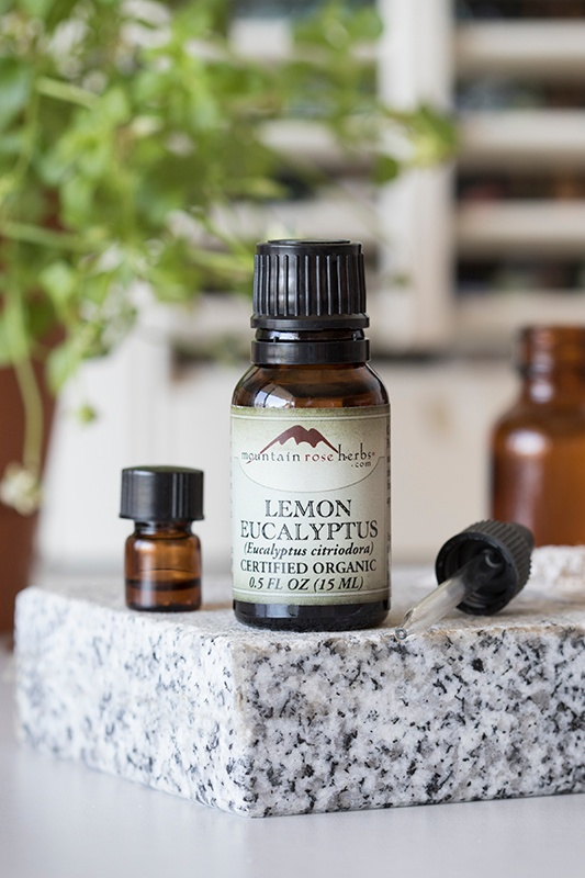 .5 oz bottle of lemon eucalyptus essential oil with small bottle and dropper on granite counter