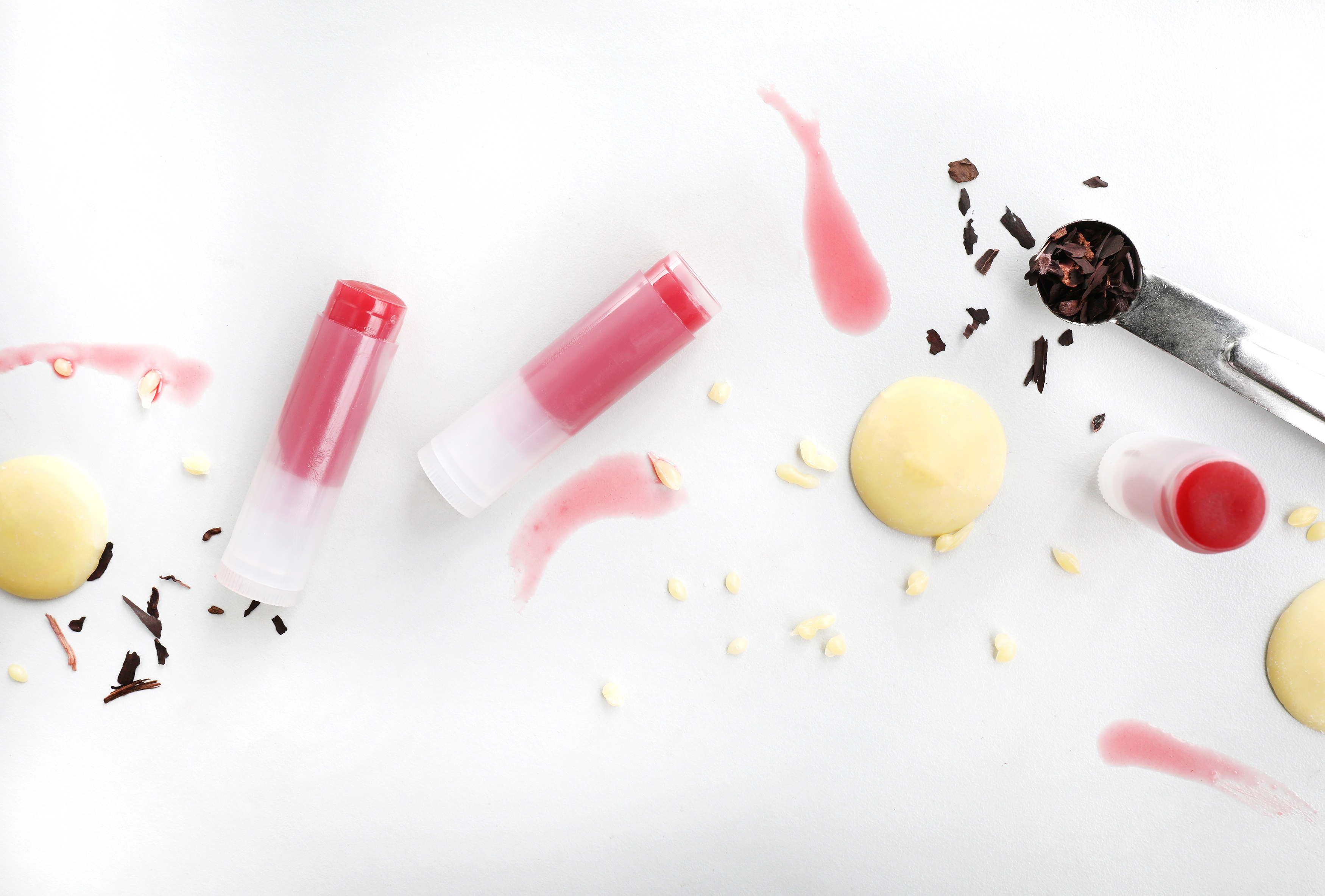Bright pink and red lip balm tubes laying out on counter with butter and beet root pieces