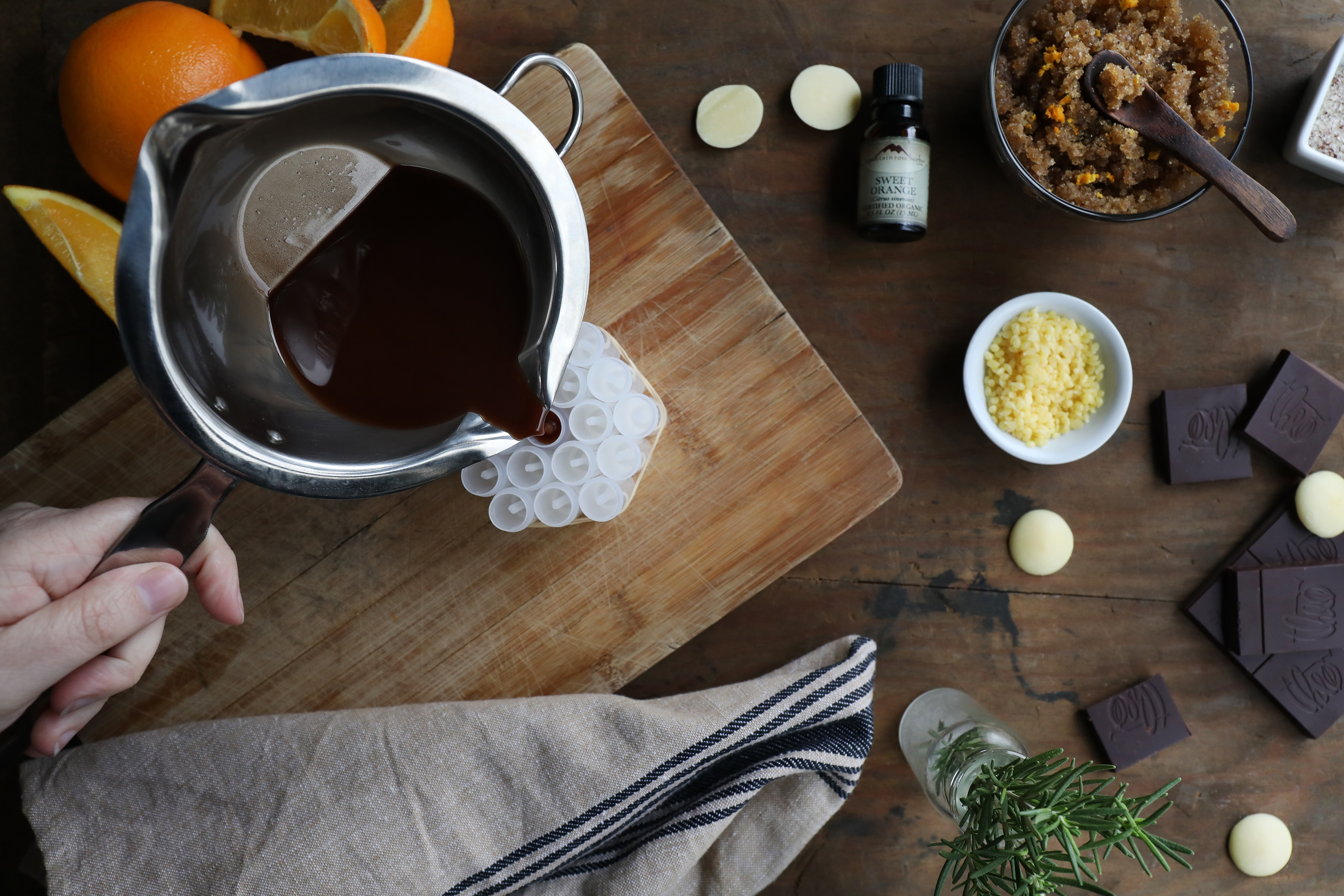 Hand pouring dark colored liquid into lib balm tubes with fresh citrus and rosemary and other ingredients surround it.