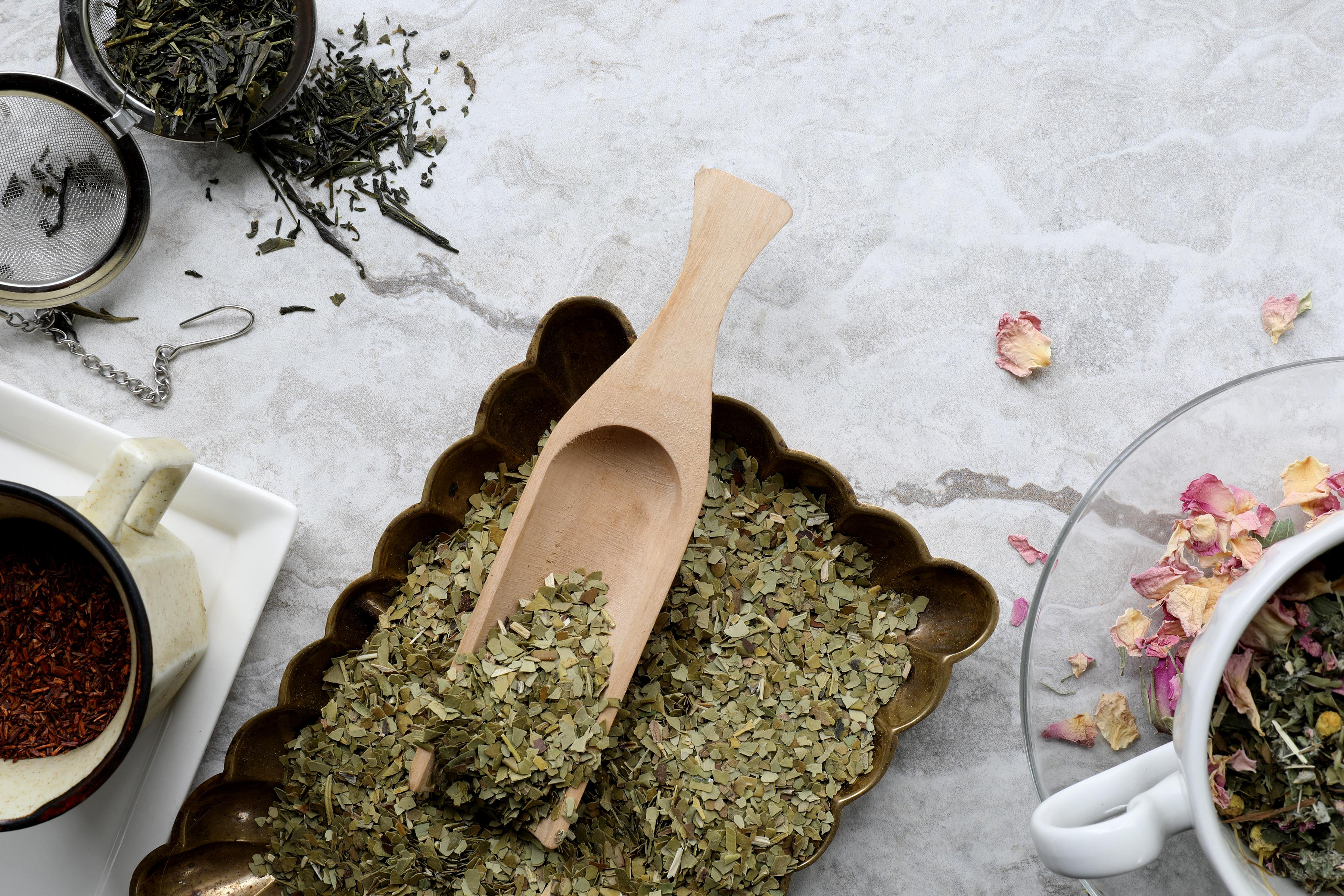 Wooden tea spoon in bowl filled with loose-leaf mate tea near brewing supplies